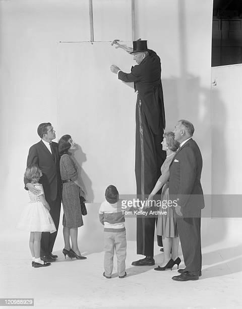 Familie watching uncle sam hammering Nagel auf Mauer