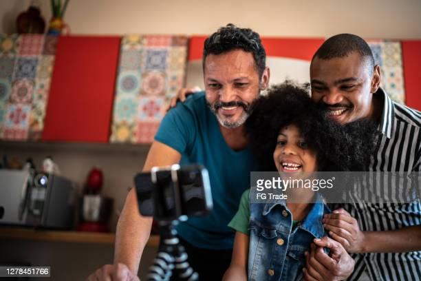 família assistindo vídeo / filme no smartphone e se divertindo em casa - pessoa gay - fotografias e filmes do acervo
