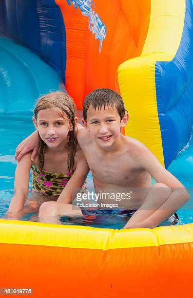 family water slide in back yard at home with water in summer with boy 10 and girl 7 brother and sister playing fun