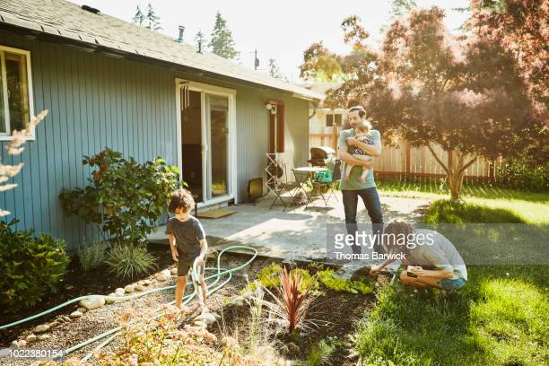 family watering garden in backyard on summer morning - spuiten activiteit stockfoto's en -beelden
