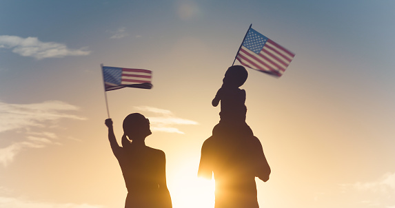 Family waving American flags 1183702115