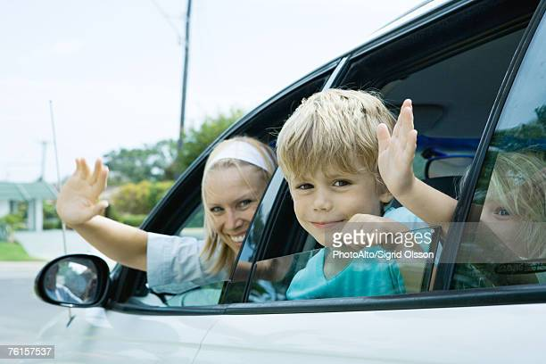 Family waving from car windows