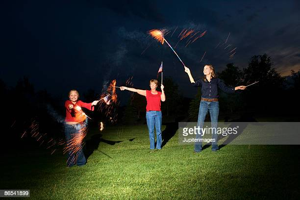 Family waving sparklers and American flags at night