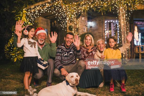 family waving their hands while sitting outdoors - hello december stock pictures, royalty-free photos & images