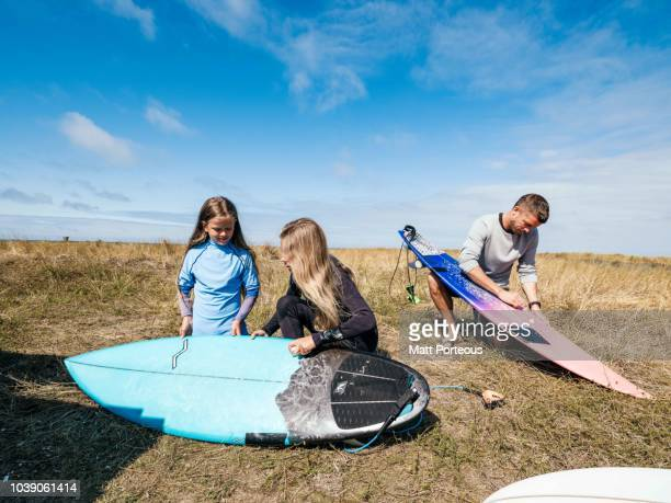 Family wax their surfboards