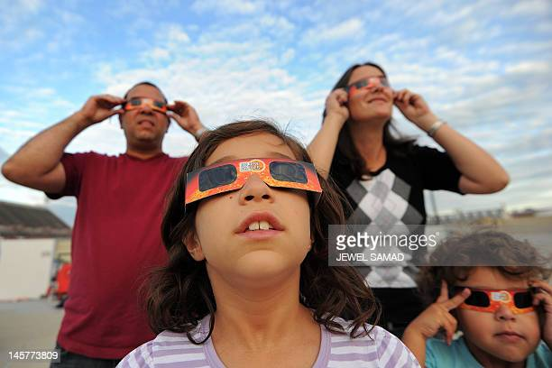 A family wear special goggles to watch Venus crossing the sun's face on June 5 2012 as seen from College Park Maryland Astronomers around the world...