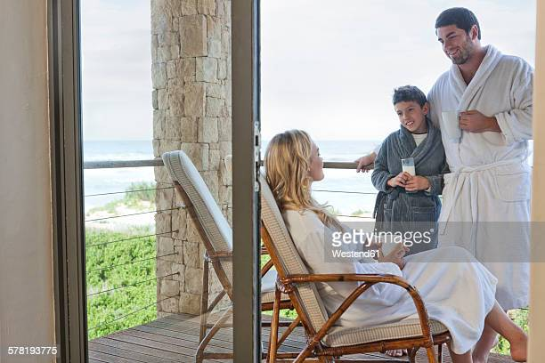 Family wearing bathrobes on patio of beach house