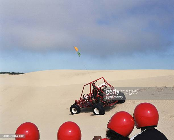 Family wearing crash helmets, looking at dune buggy, rear view