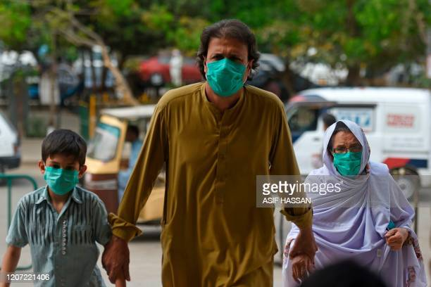 Family wearing facemasks amid concerns over the spread of the COVID-19 novel coronavirus, arrive at the railwaystationin Karachi on March 15, 2020.