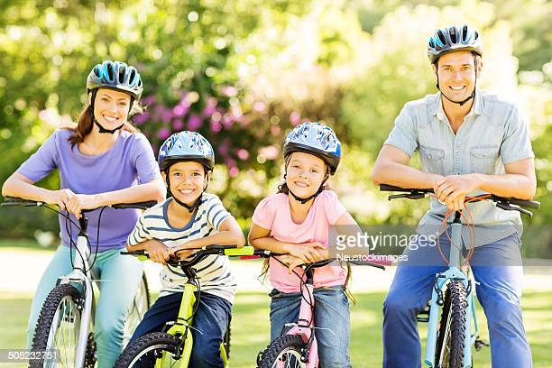 Family Wearing Helmets While Sitting On Bicycles In Park