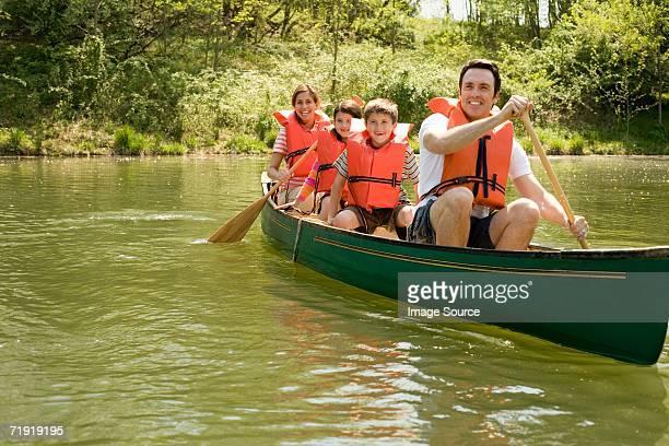 Family wearing life jacket in canoe