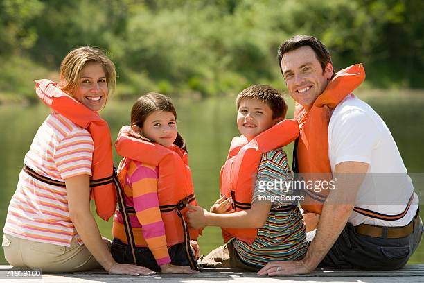 family wearing life jacket sitting on jetty - life jacket stock pictures, royalty-free photos & images