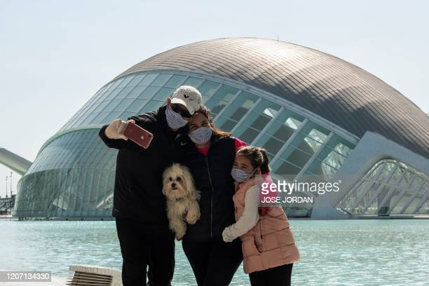 Family wearing protective masks take a selfie at the City of Arts and Sciences in Valencia on March 14, 2020 as Spain confirmed more than 1,500 new...