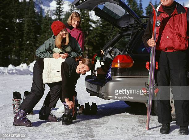 Family wearing ski clothing by car in mountains