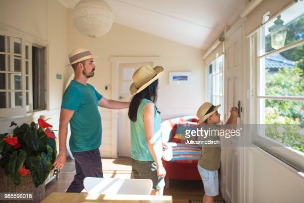 family wearing straw hats in house - mid adult men stock pictures, royalty-free photos & images
