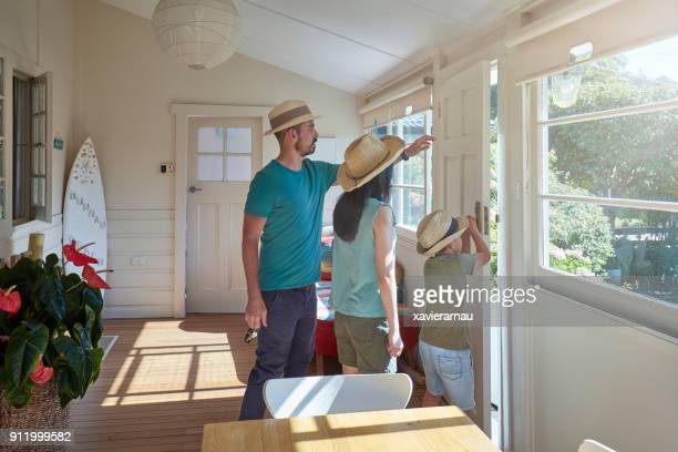 Family wearing straw hats standing in house