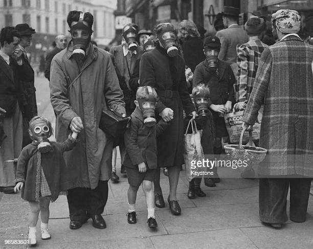 A family wearing their gas masks to the shops during a gas drill in Richmond Surrey 31st May 1941 The drill involved a canister of tear gas to...