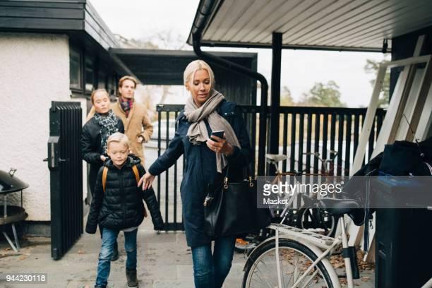 family wearing warm clothing walking in back yard - familie mit zwei kindern stock-fotos und bilder
