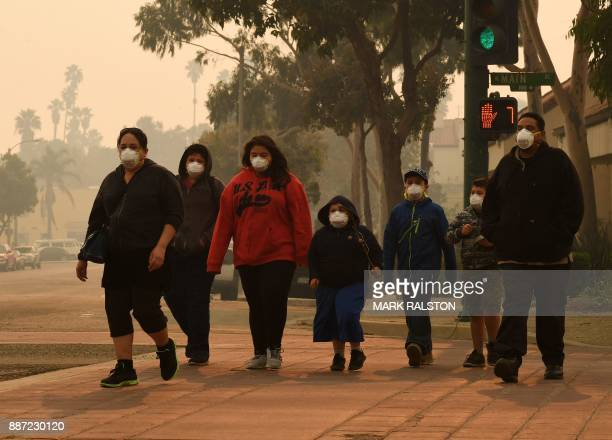 TOPSHOT A family wears face masks as they walk through the smoke filled streets after the Thomas wildfire swept through Ventura California on...