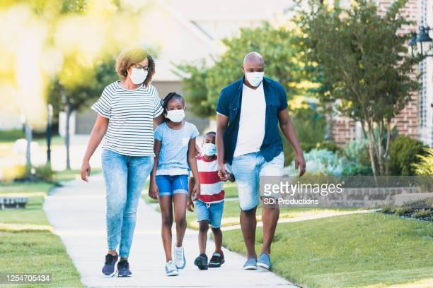 familie draagt gezichtsmaskers tijdens covid-19 pandemie - wandelen lichaamsbeweging stockfoto's en -beelden