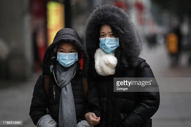 A family wears masks while walking in the street on January 22 2020 in Wuhan Hubei province China A new infectious coronavirus known as 2019nCoV was...