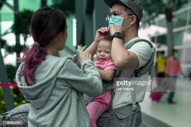 A family wears their masks at the Kuala Lumpur International Airport 2 on February 4 2020 in Kuala Lumpur Malaysia The coronavirus originating in...