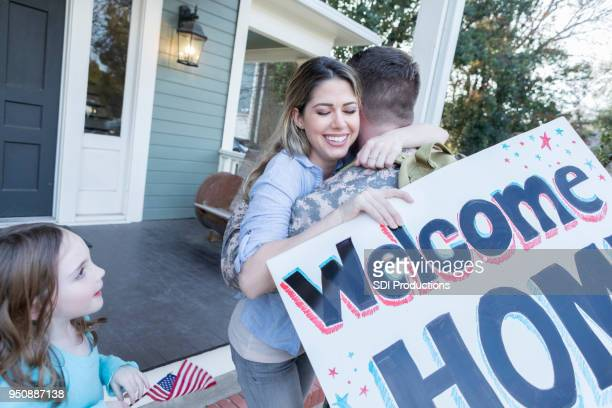 family welcomes soldier dad home from duty - military spouse stock pictures, royalty-free photos & images