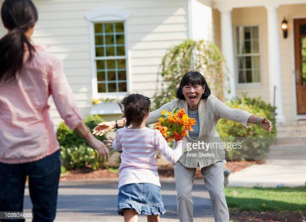 family welcoming woman with flowers - visita imagens e fotografias de stock