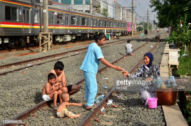 A family who lives next to railway tracks purchases traditional medicine in Bekasi West Java on April 3 as a preventive measure against the COVID19...