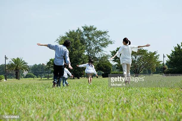 Family who mimics airplane in park and runs