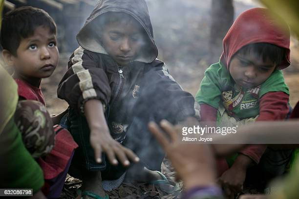 A family who recently fled violence in Salipara village in Myanmar warm themselves by a fire in the Balu Kali Rohingya refugee camp on January 19...