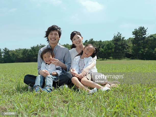 Family who sits on lawn in park