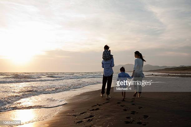 Family who strolls on beach of evening