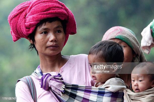 A family who was forced by the Burmese army to abandon its village stand in a field in the jungle of the Northern Karen State