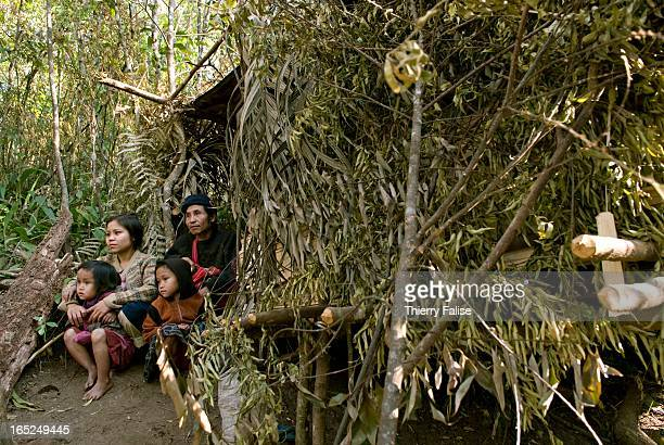 A family who was forced by the Burmese army to abandon their village sits in front of a hut made from leaves and branches in the jungle of the...