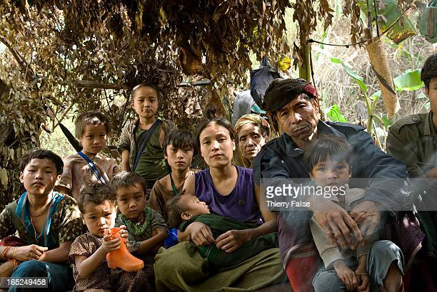 A family who was forced by the Burmese army to abandon their village sits in a hut made from leaves and branches in the jungle of the Northern Karen...
