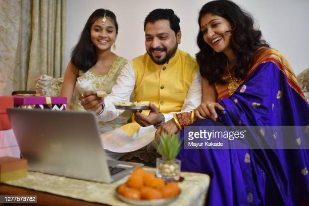 family wishing happy diwali to their friends and relatives over a video call - diwali stock pictures, royalty-free photos & images