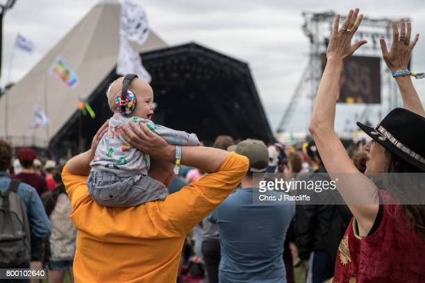 A family with a baby wearing ear defenders on his fathers shoulders watch Hacienda Classical on the Pyramid stage at Glastonbury Festival Site on...