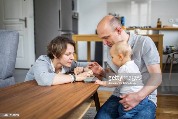 Family with a child playing on a tablet