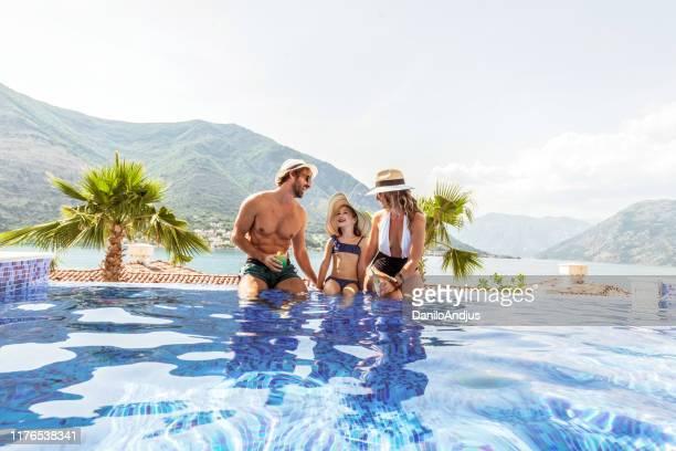 famille avec une fille ayant l'amusement dans la piscine - station de vacances photos et images de collection