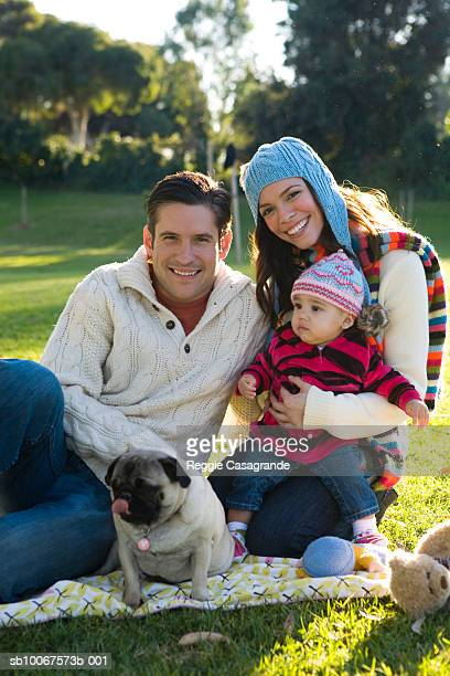 family with baby boy (6-11 months) and pug sitting in park, portrait - 6 11 months stock pictures, royalty-free photos & images