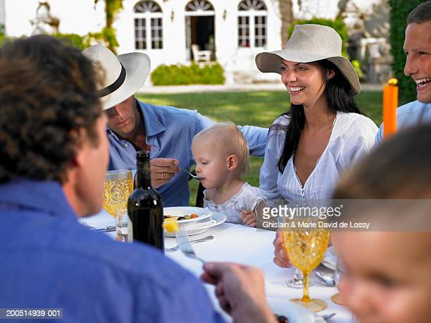Family with baby girl (9-12 months) and toddler boy (18-24 months) having meal on table on lawn