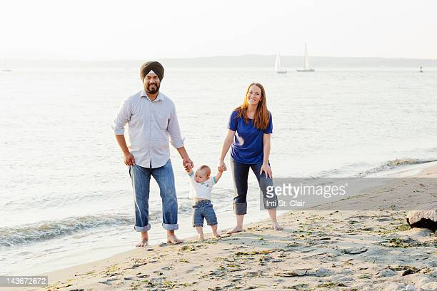 family with baby walking together on then beach - rolled up trousers stock pictures, royalty-free photos & images