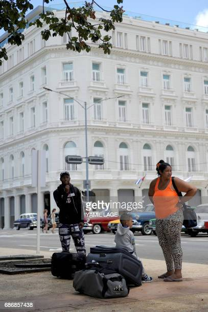 A family with baggage wait for a bus near the Manzana Kempinski Hotel the first luxury five star plus tourist facility in Cuba on May 22 2017 / AFP...