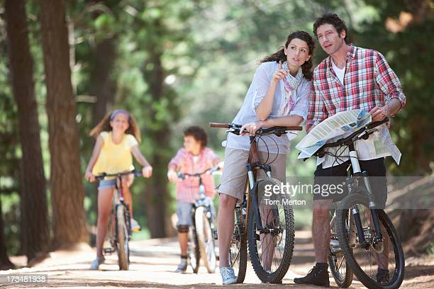 family with bicycles looking at map in woods - 30 39 years stock pictures, royalty-free photos & images