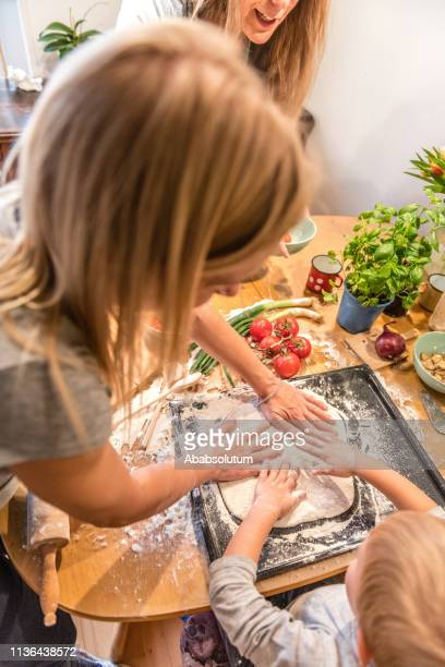 family with blond boy preparing vegetarian pizza at home - vegetarian pizza stock pictures, royalty-free photos & images