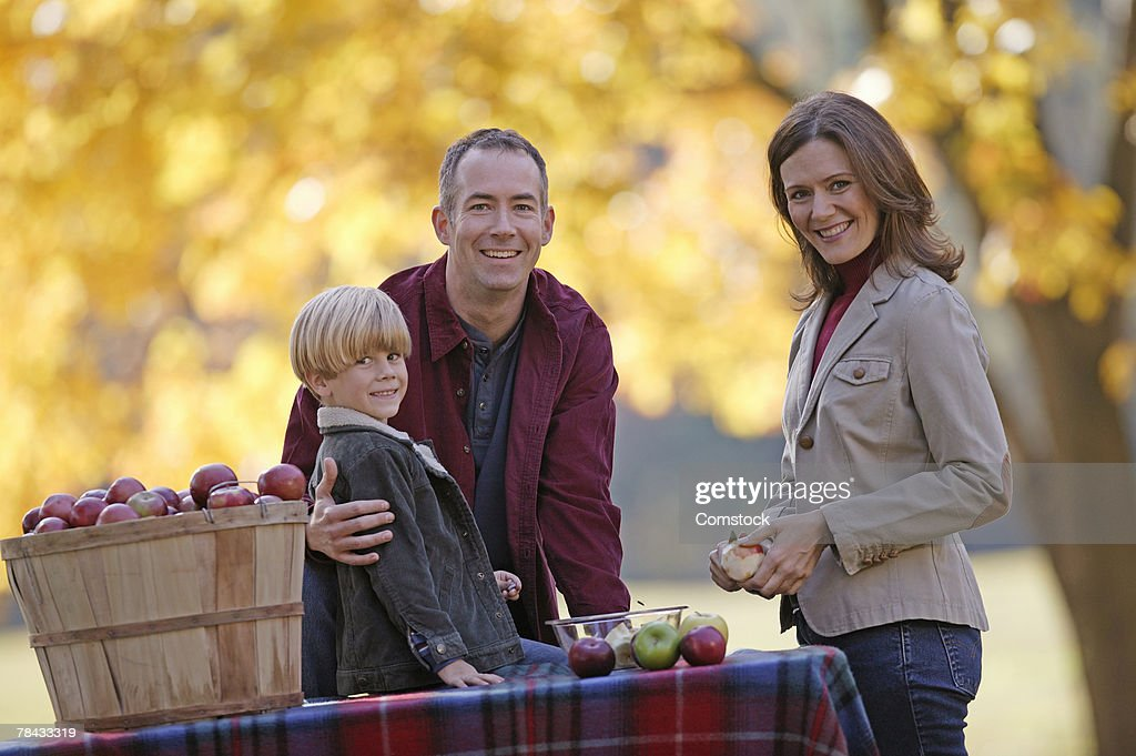 Family with bushel of apples outdoors : Stockfoto
