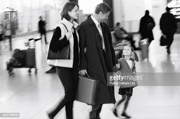 Family with businessman at airport