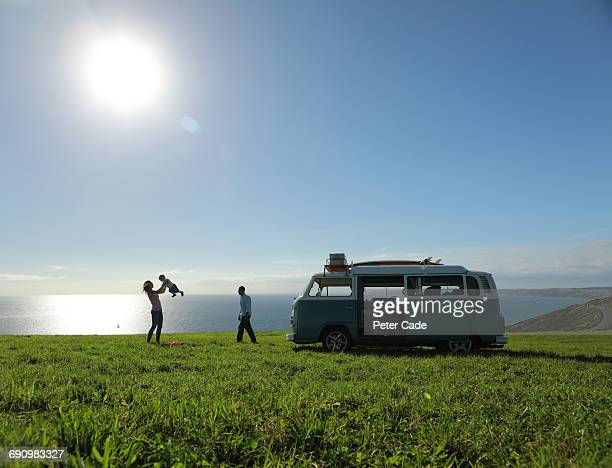 family with camper in field by sea - camper van stock pictures, royalty-free photos & images