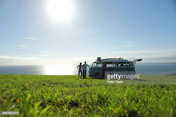 family with camper in field looking at sea - distant stock pictures, royalty-free photos & images